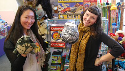 Connie and Chloe hold up items from the Discovery Corner Toy & Bookstore