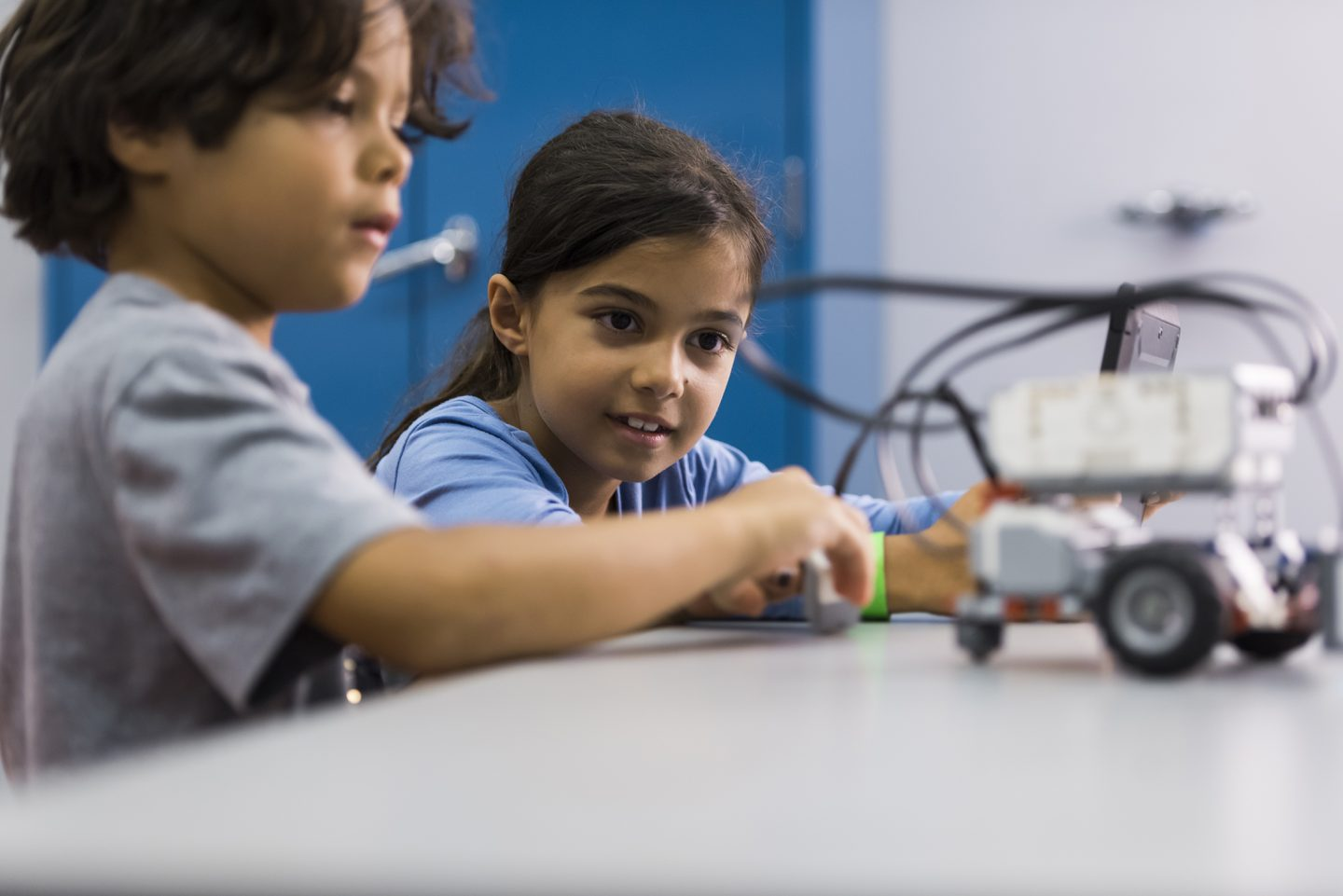 Two children working on a robot car