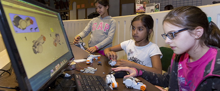 Three students working on a science project and looking at a computer screen.