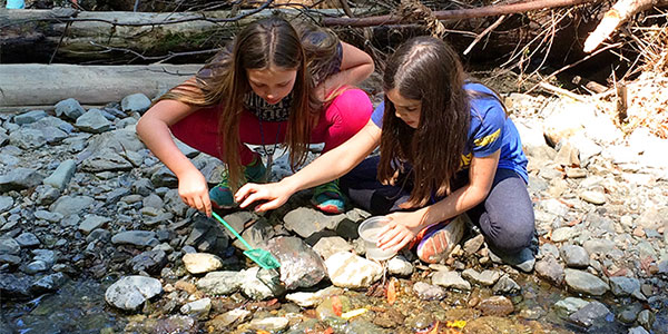 Two children examining rocks in nature