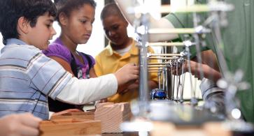 Children conducting a science experiment building bridges and using a model car