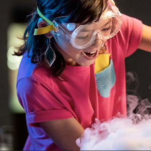 A young person wearing safety goggles pours liquid during a science demonstration