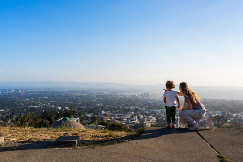 A young child and an adult looking out at the view of the city down below