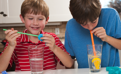 Two children with straws and glasses they are using to illustrate a heart valve