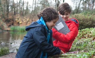 Two young people investigating nature outdoors near a lake.
