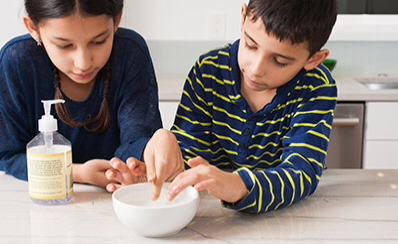 Two young people examining a bowl of water while learning about water bugs