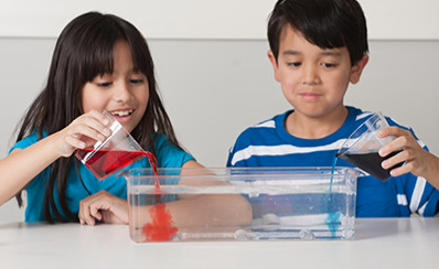 Two children pouring liquids into a glass pan.