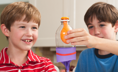 Two students building a lung out of a bottle and a balloon in a science experiment