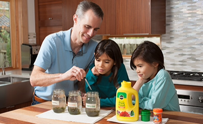 Two children and an adult examining jars of lake water.