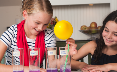 A young person holds a balloon in a science experiment about what's in your breath