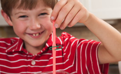 A child holding up a straw and a paperclip to simulate clogged arteries