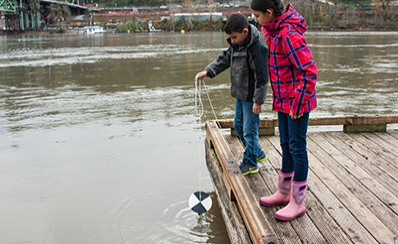Two young people investigating a lake.