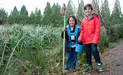 Two young people outdoors carrying a bucket and a net for a science experiment.