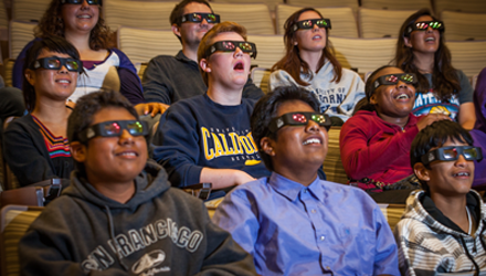 People sitting in a theater with 3D glasses watching a film