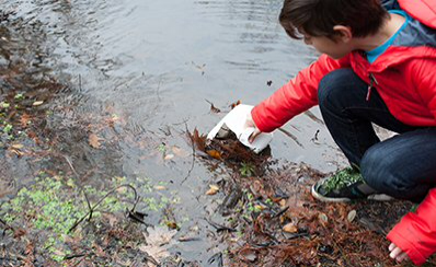 A young person examining a lake.