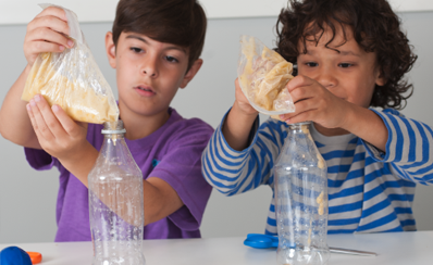 Two children pouring a mashed banana into plastic bottles for their science experiment