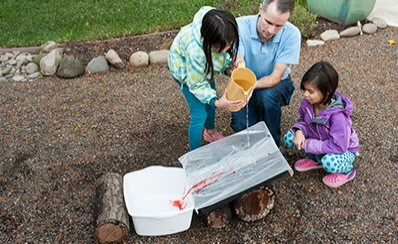 Two children and an adult pouring lake water into a bucket for a science experiment.