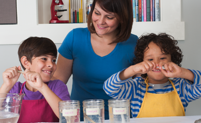 An adult and two children conducting a science experiment about stiff and bendy bones