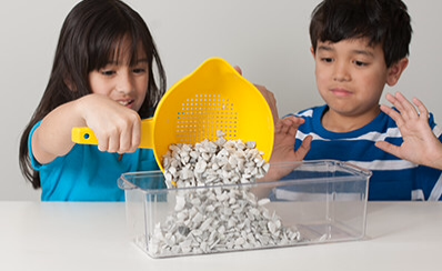 Two children pouring small stones into a glass pan.
