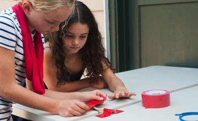 Two young people using tape in their science experiment about weak and strong bones