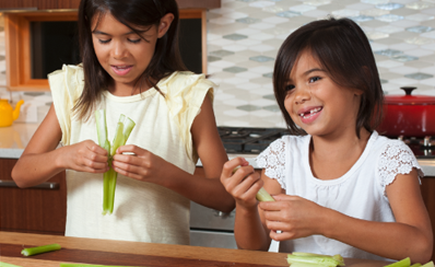 Two children holding celery that they are using for their science experiment about bone fractures