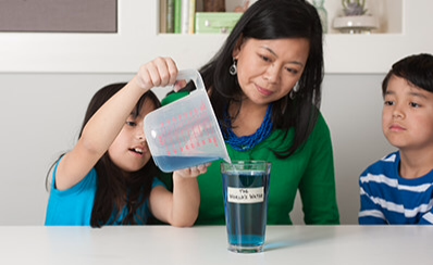 A child pouring liquid into a glass with an adult and another child watching.