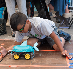 A young person testing a constructed robot car