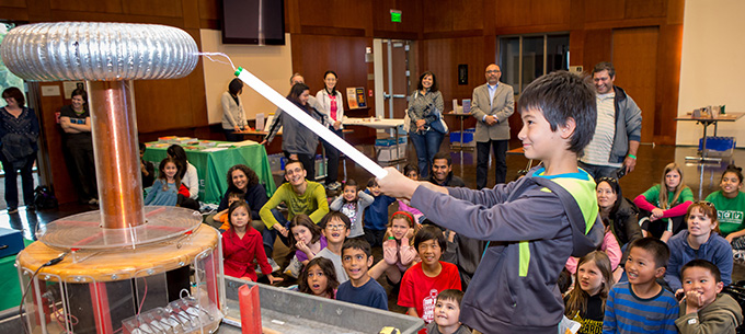 A young scientist experiments with the Hall's Tesla Coil in front of a crowd.