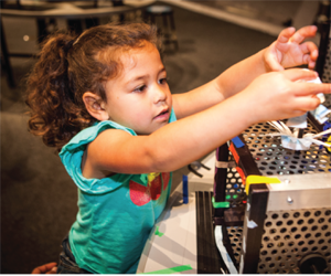 A child examining a scientific machine with gears