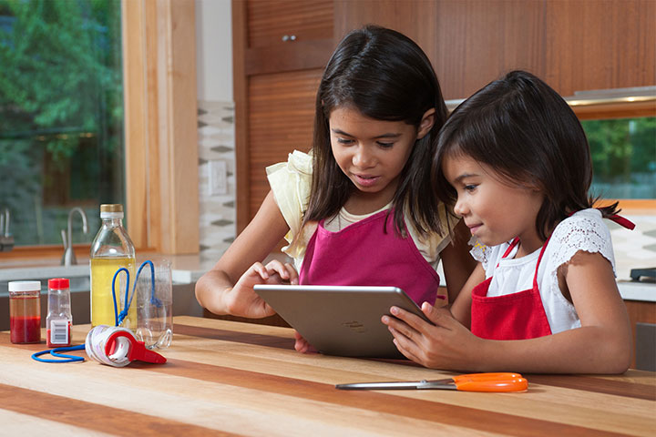 Two children using an app on their tablet.