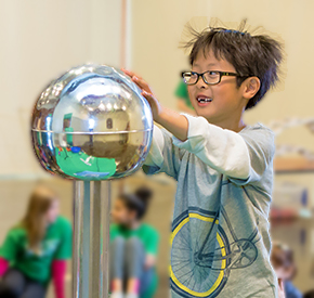 A child participating in a Science Show activity and learning about static electricity