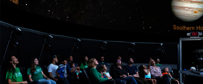 A group of people sitting in the planetarium and looking up at the stars
