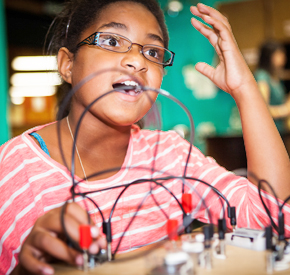A young person working on a science project at summer camp