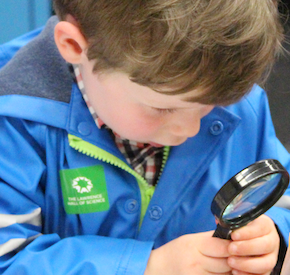 A child looking through a magnifying glass