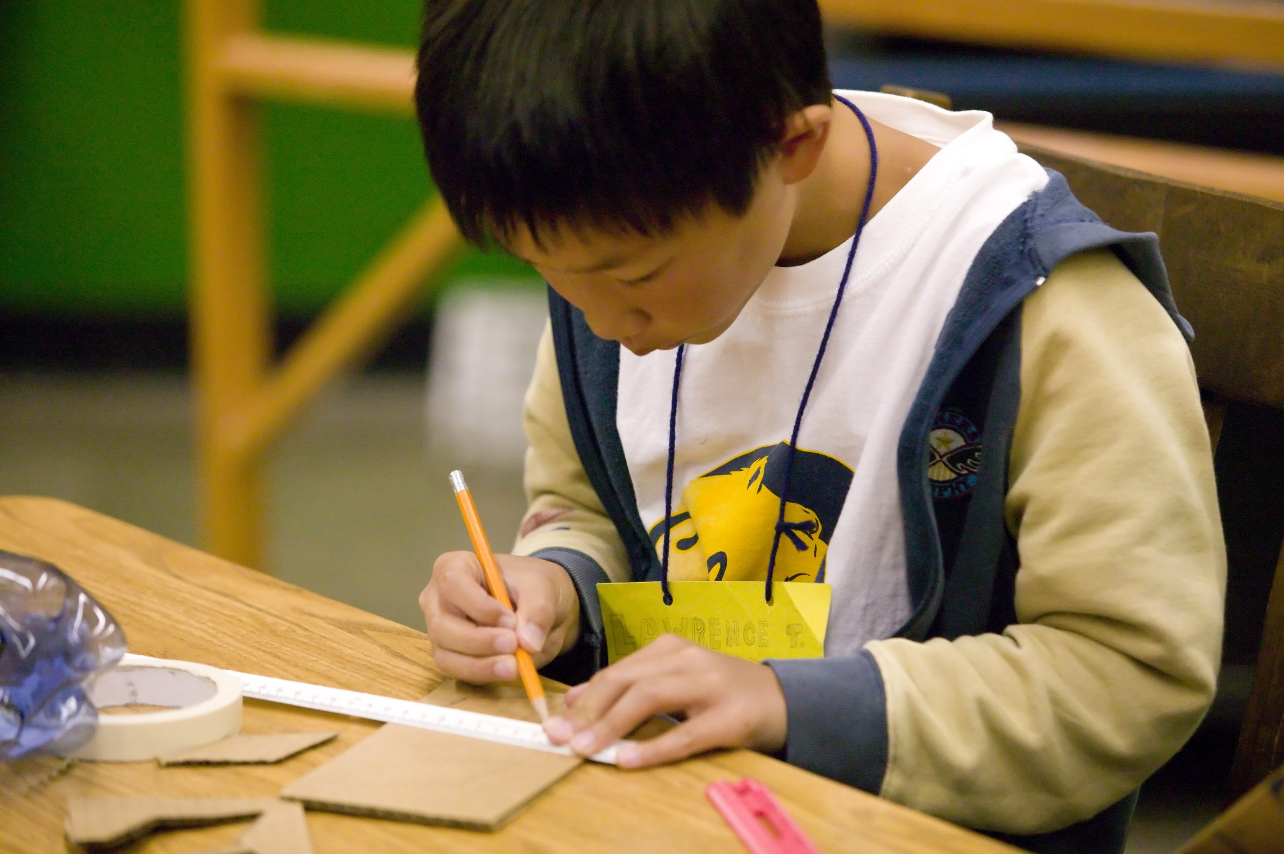 A student drawing a line with a ruler
