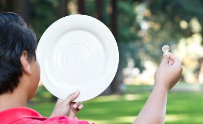 A child holding up a plate and a coin