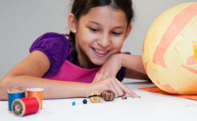 A young person is making a model of the sun and the earth.