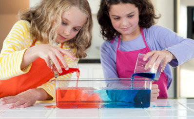 Two young people are pouring red and blue liquids into a glass pan.
