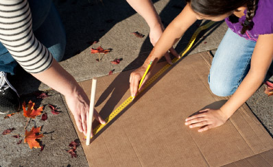 A view of two sets of hands as they draw a line using a tape measure