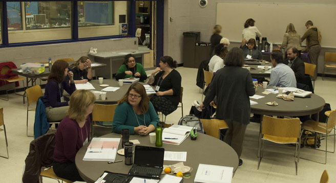 Teachers at a workshop sitting in at tables in groups.