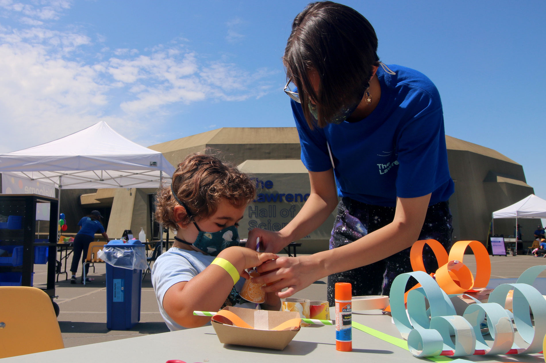 A staff member helping a child with a paper sculpture during Summer Fundays