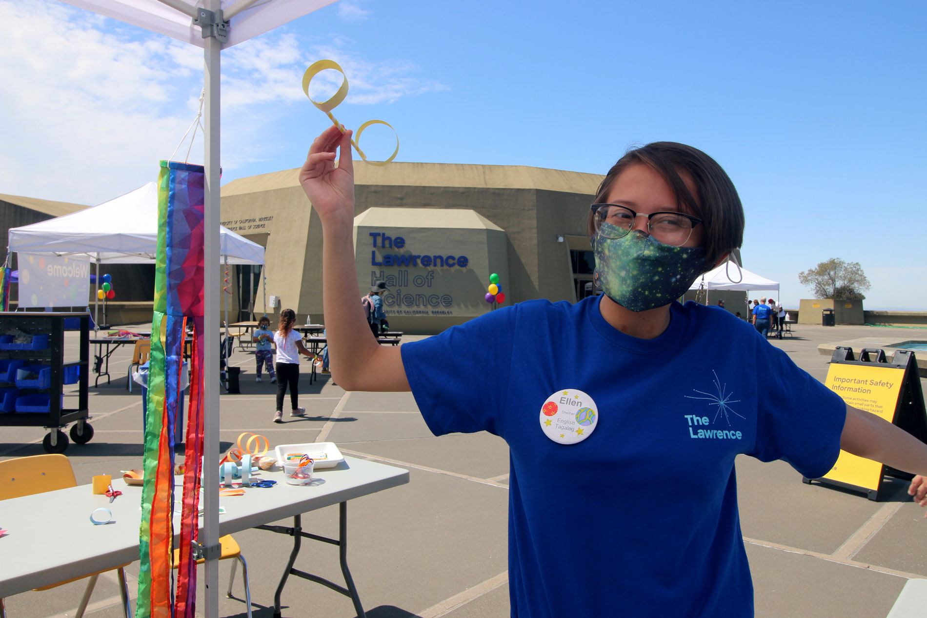 A staff member holding up a paper sculpture during Summer Fundays at The Lawrence