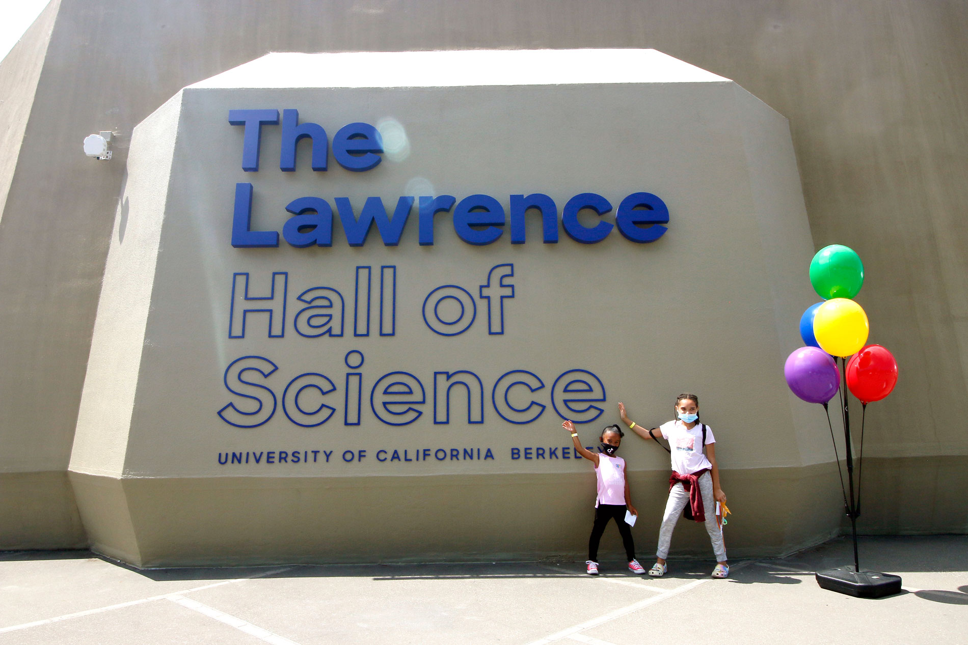 Two children standing at The Lawrence Hall of Science sign on the plaza