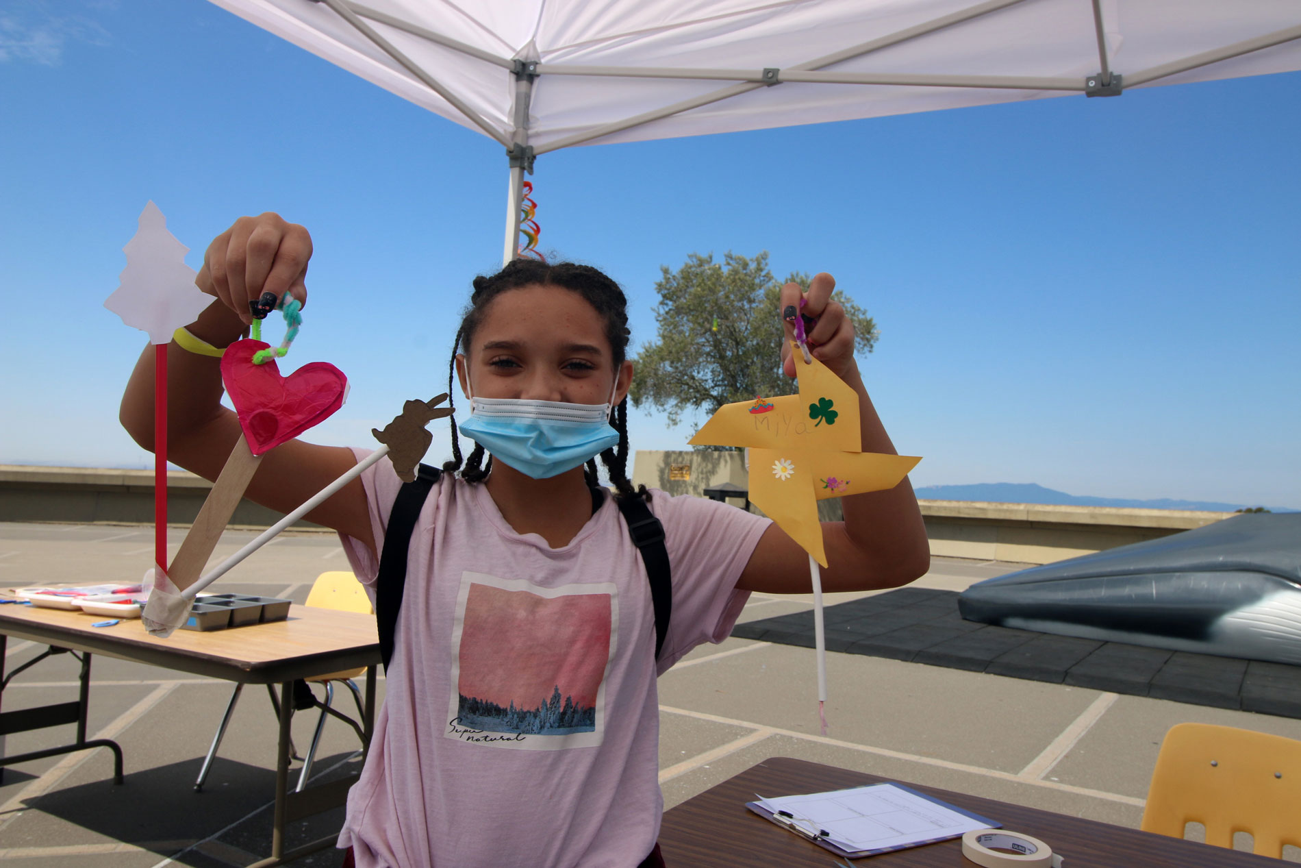 A young person holding up her paper sculptures she made during Summer Fundays