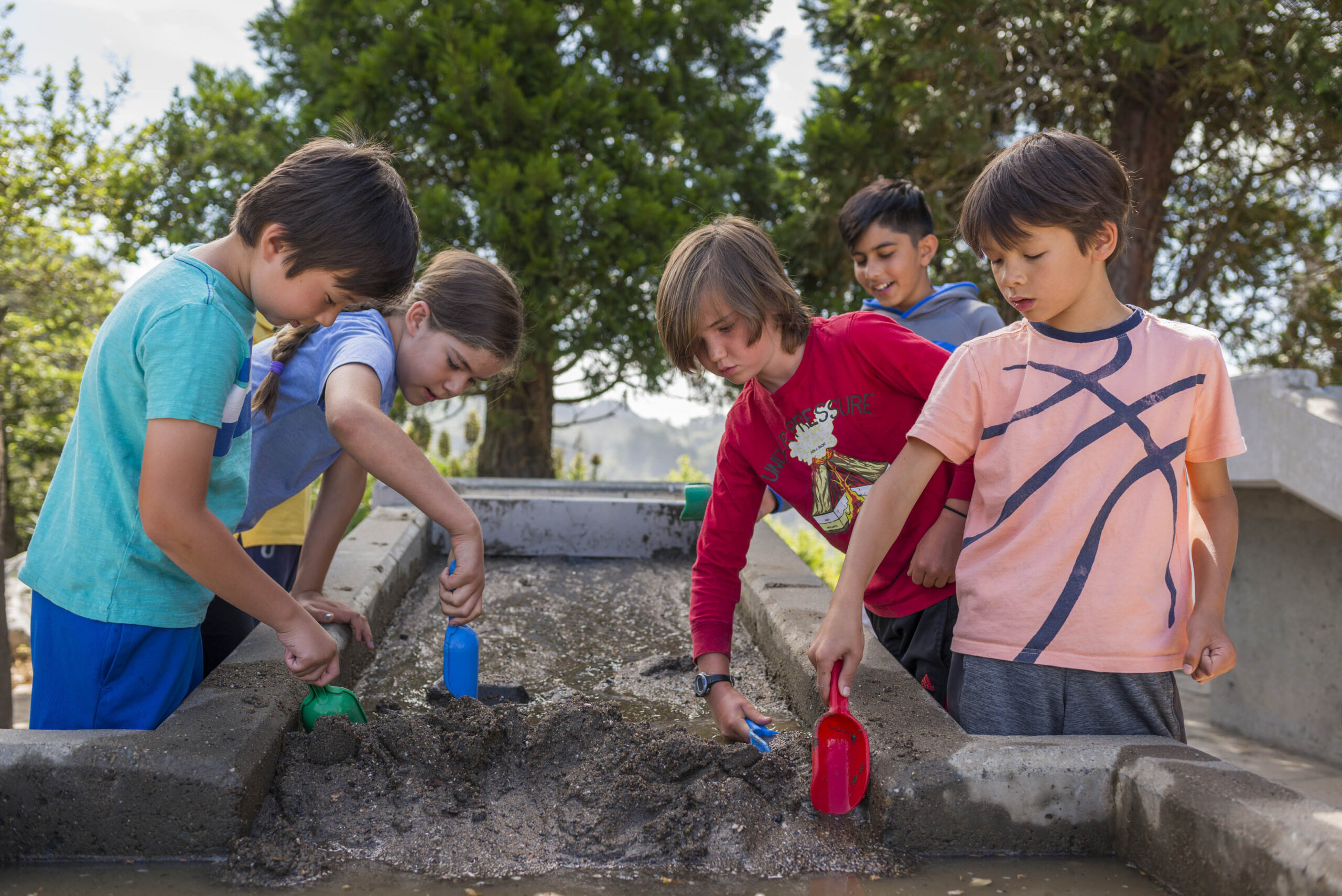 Five children digging in sand in the Forces that Shape the Bay exhibit
