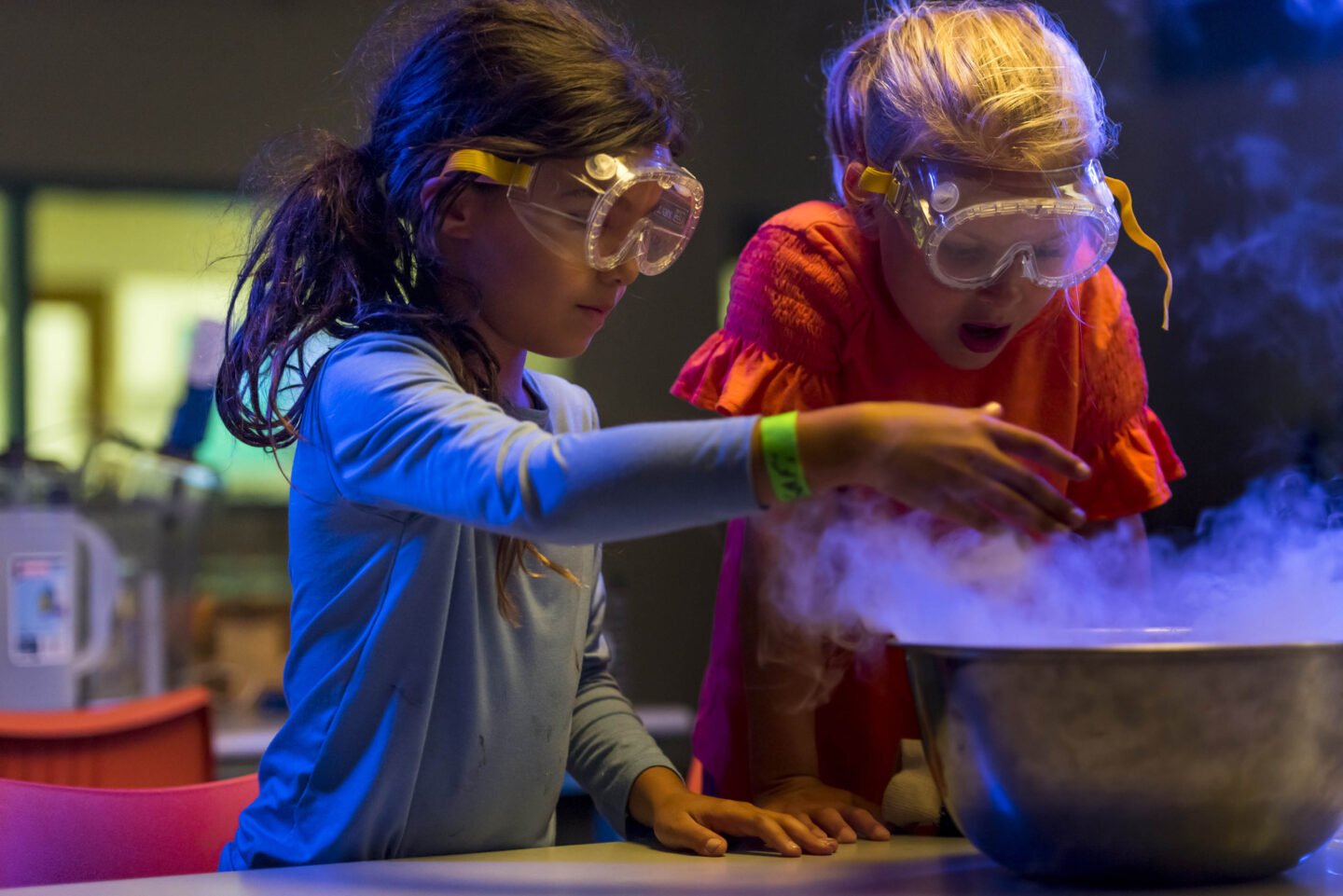 Two young people wearing safety goggles conducting a science experiment.