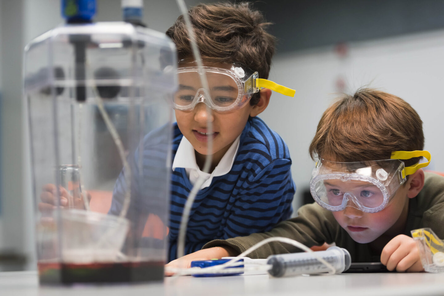 Two children wearing safety goggles examining their results in a science experiment