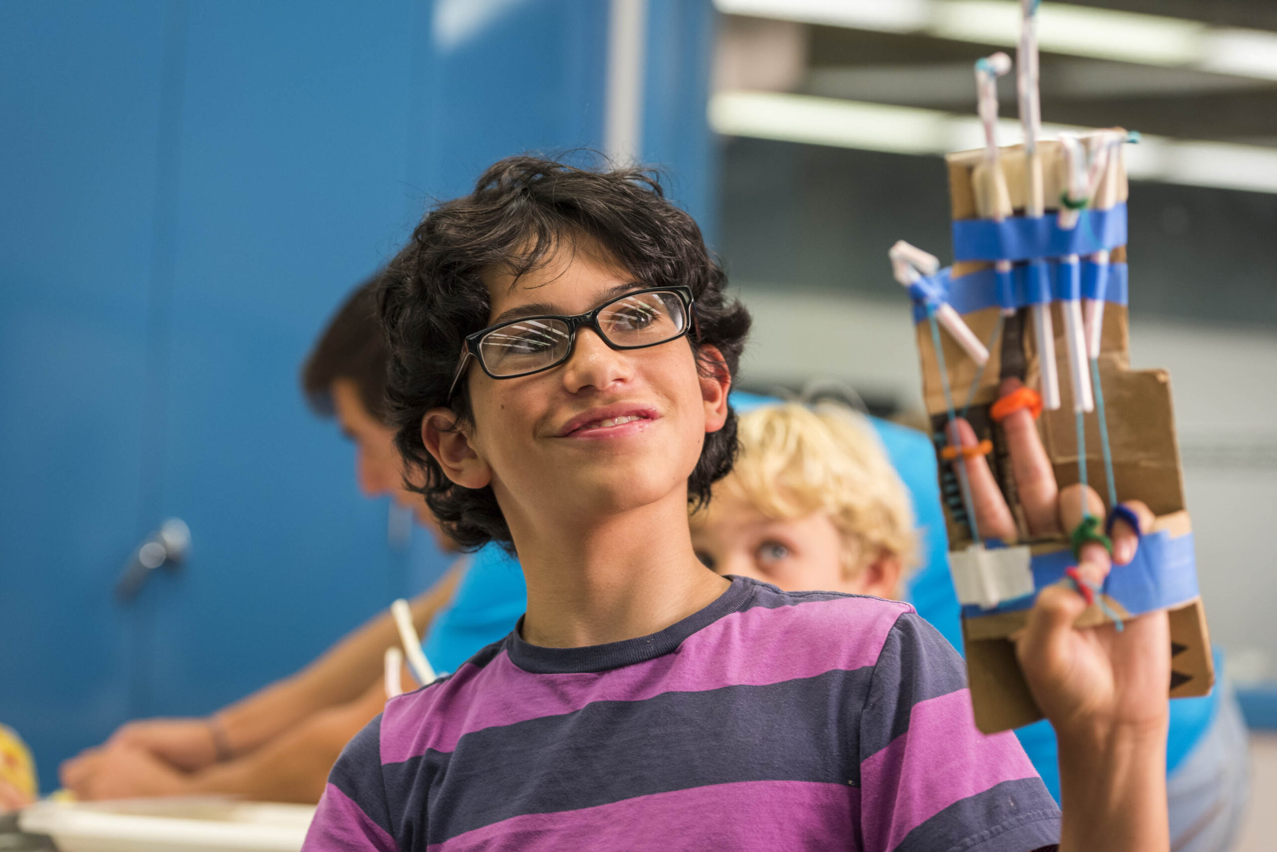 A student holding up his invention
