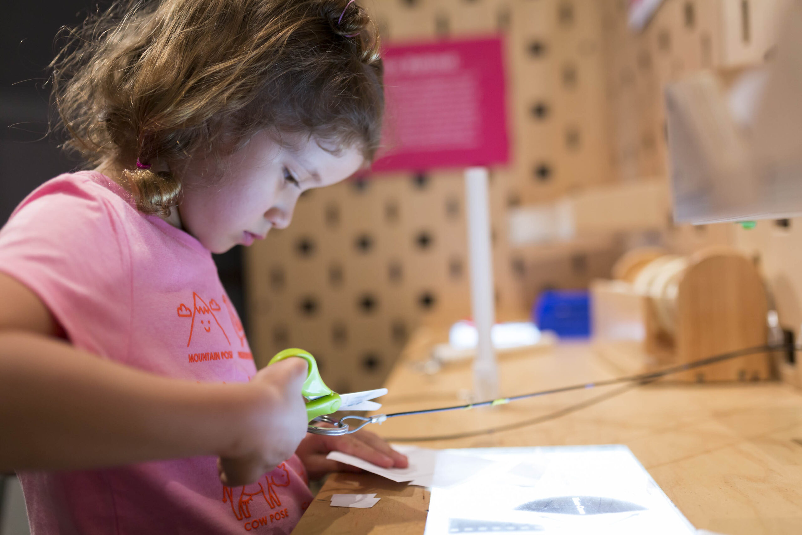 A child creating her own invention at the Make Station exhibit