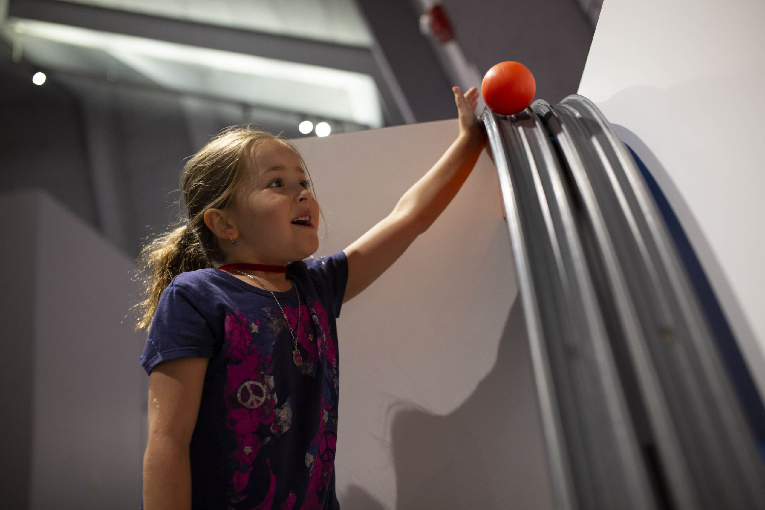 A young child setting a ball at the top of a ramp